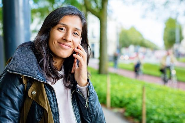 Mulher jovem, usando, telefone móvel, parque