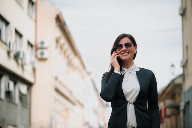 Mulher jovem, usando, telefone móvel, rua