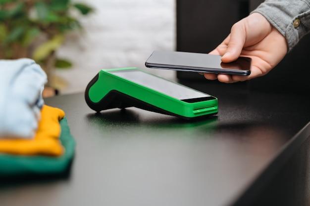 Mulher jovem usando terminal de pagamento e telefone celular com tecnologia nfc para pagamentos sem dinheiro