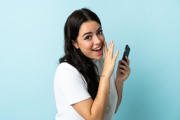 Mulher jovem usando um celular isolado em um fundo azul e sussurrando algo