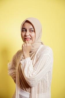Mulher jovem usando um hijab com uma expressão de nojo isolada em um fundo amarelo