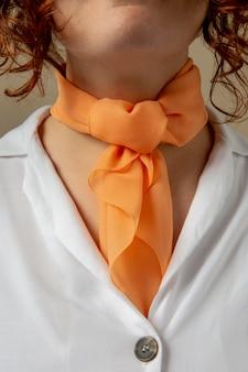 Mulher jovem usando um lenço como acessório para o pescoço
