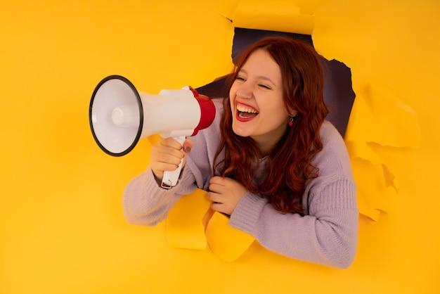 Mulher jovem usando um megafone para levantar a voz através de um buraco na parede de papel. conceito de publicidade e promoção.