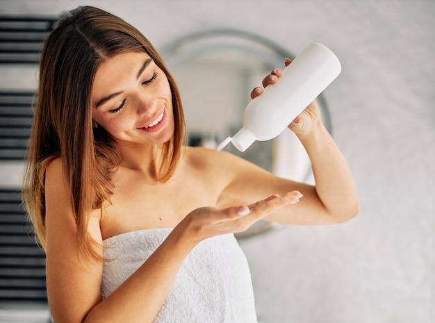 Mulher jovem usando um pouco de loção para a pele