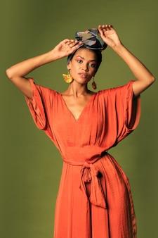 Mulher jovem usando um vestido laranja com turbante e joias étnicas