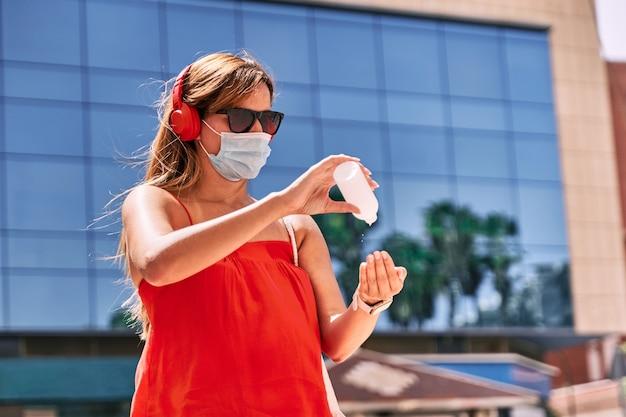 Mulher jovem usando uma máscara com gel desinfetante nas mãos na cidade