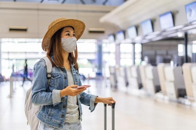 Mulher jovem usando uma máscara facial e segurando um telefone celular está procurando um balcão de check-in no aeroporto