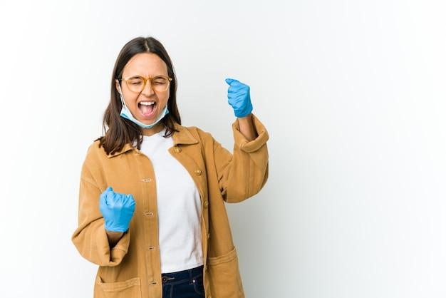Mulher jovem usando uma máscara para se proteger de cobiça isolada na parede branca levantando o punho após uma vitória, conceito vencedor
