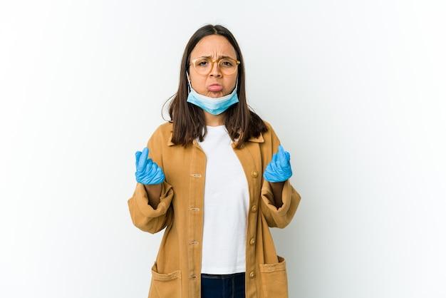Mulher jovem usando uma máscara para se proteger de cobiça isolada na parede branca, mostrando que não tem dinheiro