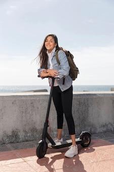 Mulher jovem usando uma scooter ao ar livre