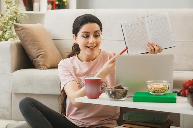 Mulher jovem usou laptop segurando e aponta com uma caneta para um caderno sentado no chão atrás da mesa de centro na sala de estar