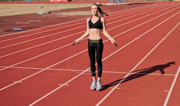 Mulher jovem velocista no sportswear pulando com corda na pista do estádio com revestimento vermelho em dia ensolarado