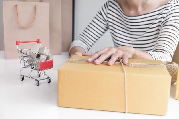 Mulher jovem vendedor preparando o pacote a ser enviado transporte de correio para convenien cliente