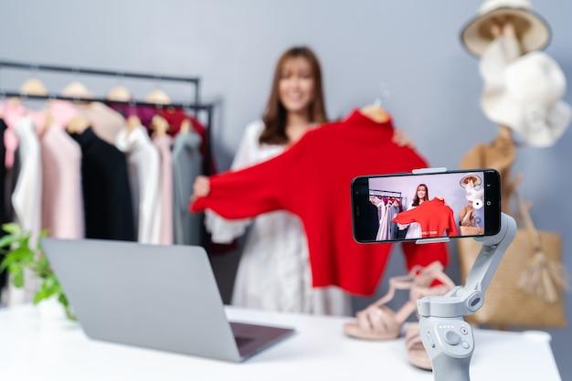 Mulher jovem vendendo roupas on-line por streaming ao vivo em smartphone, e-commerce empresarial on-line em casa