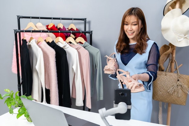Mulher jovem vendendo sapatos e roupas on-line por streaming ao vivo em smartphone, e-commerce empresarial on-line em casa