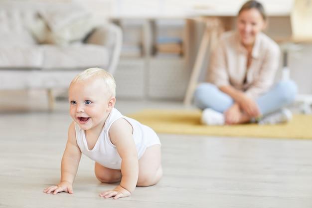 Mulher jovem vendo seu filhinho alegre rastejando de quatro em casa