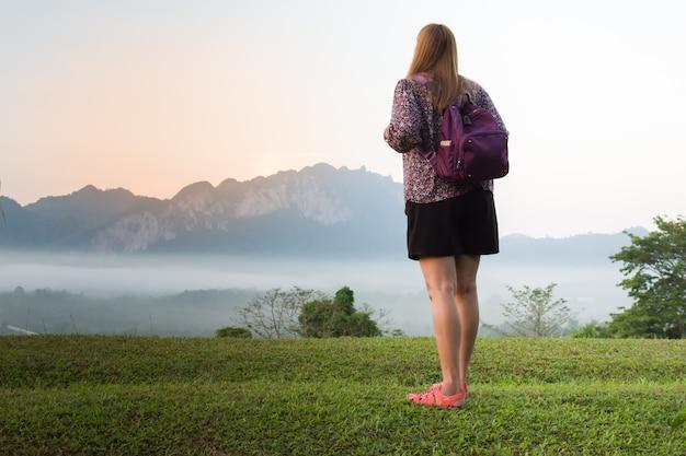 Mulher jovem, ver, vista, de manhã, com, bonito, montanhas, e, mar, nuvens
