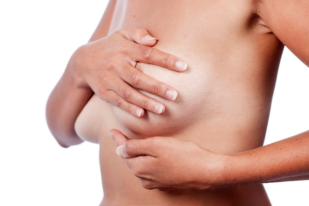 Mulher jovem verificando a mama (auto-exame) em busca de anomalias, nódulos ou caroços estranhos para câncer de mama.