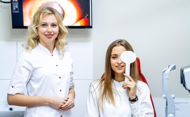 Mulher jovem verificando a visão durante um exame médico no consultório oftalmológico
