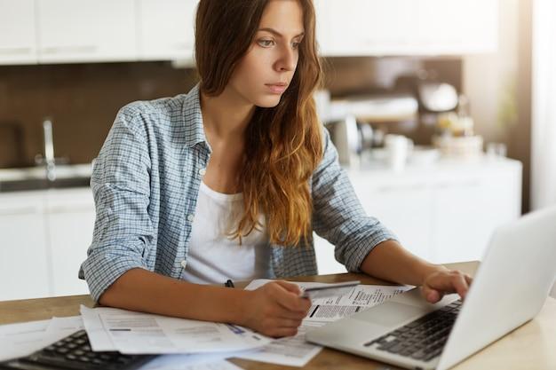 Mulher jovem verificando seu orçamento e pagando impostos