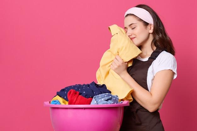Mulher jovem veste camiseta, avental marrom e faixa de cabelo, em pé com uma bacia rosa com linho limpo, cheira roupas frescas, estando satisfeita com o trabalho realizado, fica encostada na parede rosada.