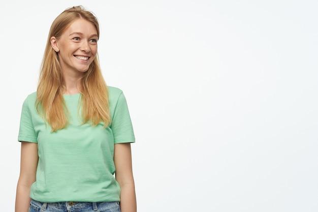 Mulher jovem, veste camiseta verde e calça jeans, sente-se feliz, sorri amplamente com expressão facial satisfeita, olha de lado