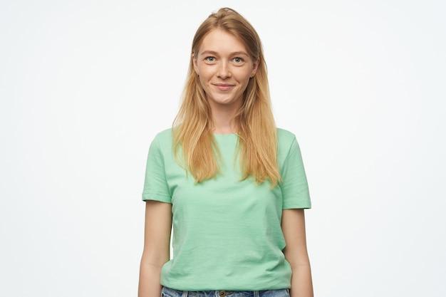 Mulher jovem, veste camiseta verde e calça jeans, sente-se feliz, sorri amplamente com expressão facial satisfeita