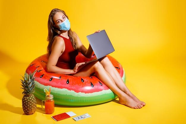 Mulher jovem vestida com maiô vermelho, sentada no círculo inflável no fundo amarelo, vestindo um m ...