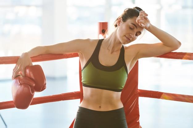 Mulher jovem vestida com roupas esportivas cansada após o treino, inclinando-se na borda do ringue de boxe enquanto toca sua testa