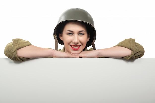 Mulher jovem, vestido, em, wwii, militar, uniforme, com, capacete, mostrando, vazio, em branco, signboard, com, um, copyspace
