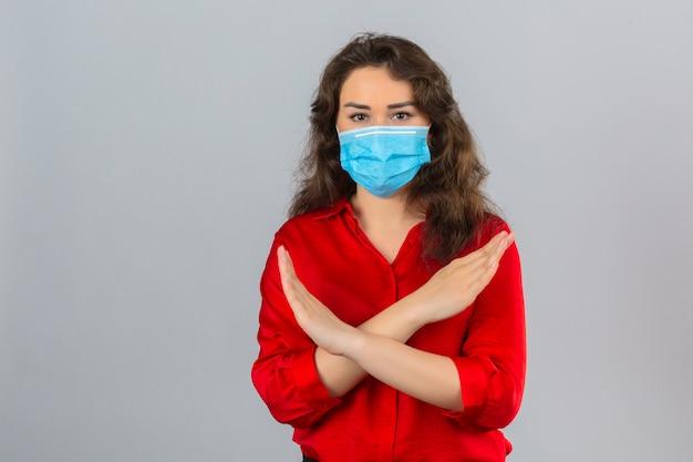Mulher jovem vestindo blusa vermelha com máscara protetora médica em pé com os braços cruzados no peito fazendo gesto de parada sobre fundo branco isolado