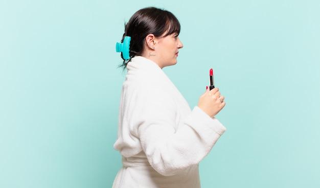 Mulher jovem vestindo roupão de banho na vista de perfil, olhando para copiar o espaço à frente, pensando, imaginando ou sonhando acordada