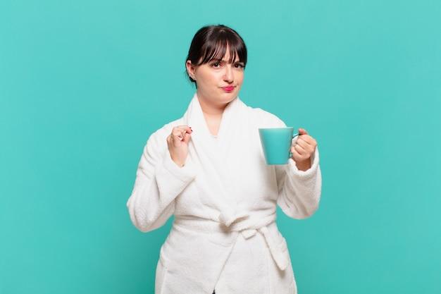 Mulher jovem vestindo roupão de banho, parecendo arrogante, bem-sucedida, positiva e orgulhosa, apontando para si mesma