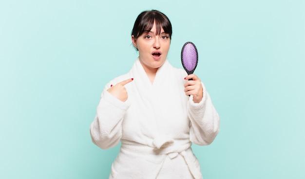 Mulher jovem vestindo roupão de banho parecendo chocada e surpresa com a boca aberta, apontando para si mesma