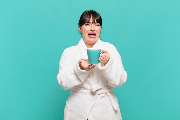 Mulher jovem vestindo roupão de banho, parecendo desesperada e frustrada, estressada, infeliz e irritada, gritando e gritando