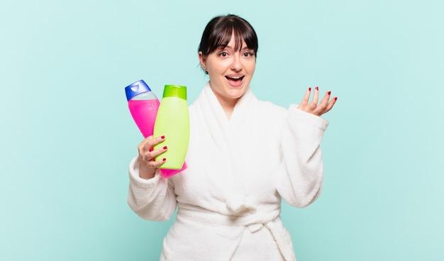 Mulher jovem vestindo roupão de banho sentindo-se feliz, surpresa e alegre, sorrindo com atitude positiva, percebendo uma solução ou ideia