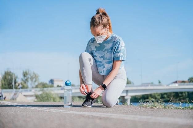Mulher jovem vestindo roupas esportivas se preparando para fazer exercícios