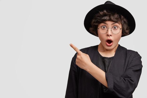 Mulher jovem vestindo roupas pretas e óculos redondos