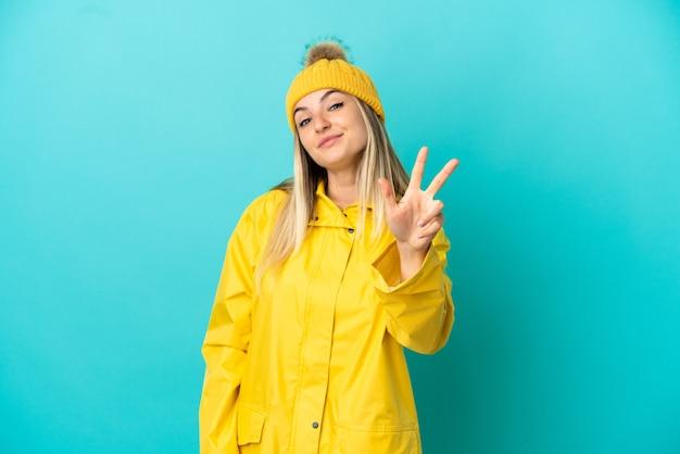 Mulher jovem vestindo um casaco à prova de chuva sobre um fundo azul isolado feliz e contando três com os dedos