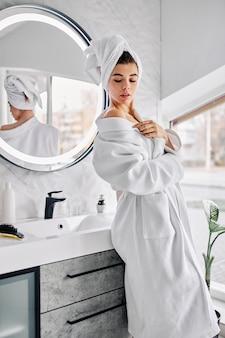 Mulher jovem vestindo um roupão de banho e uma toalha no cabelo