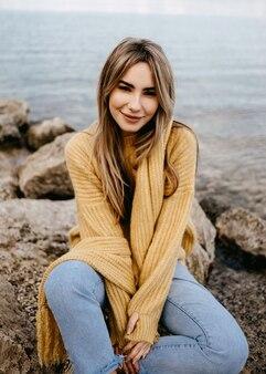 Mulher jovem vestindo um suéter amarelo, sorrindo, olhando para a câmera