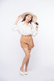 Mulher jovem vestindo uma camisa branca e shorts, usando um chapéu e alça no chapéu