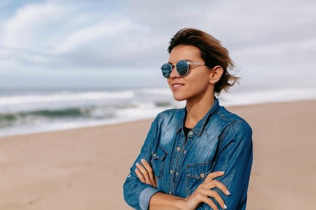 Mulher jovem vestindo uma camisa jeans e óculos de sol posando na praia