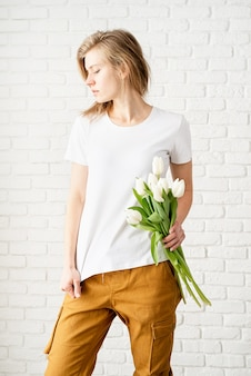 Mulher jovem vestindo uma camiseta branca em branco segurando flores de tulipas posando contra a parede de tijolos brancos