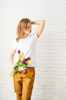 Mulher jovem vestindo uma camiseta branca em branco segurando flores em forma de tulipa posando contra uma parede de tijolos brancos