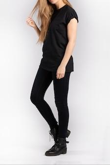 Mulher jovem vestindo uma camiseta preta de manga curta encostada em uma parede branca