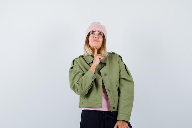 Mulher jovem vestindo uma jaqueta e um chapéu rosa