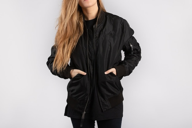Mulher jovem vestindo uma jaqueta preta encostada em uma parede branca