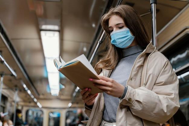 Mulher jovem viajando de metrô lendo um livro