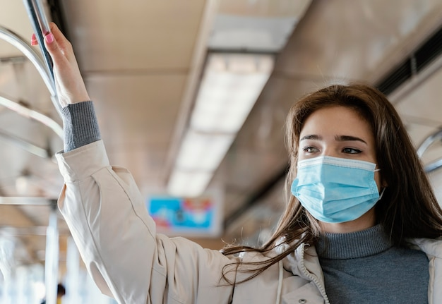Mulher jovem viajando de metrô usando uma máscara cirúrgica